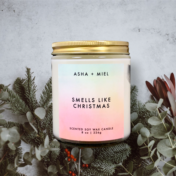 8 ounce jar soy wax candle Smells Like Christmas on background of Christmas Greenery