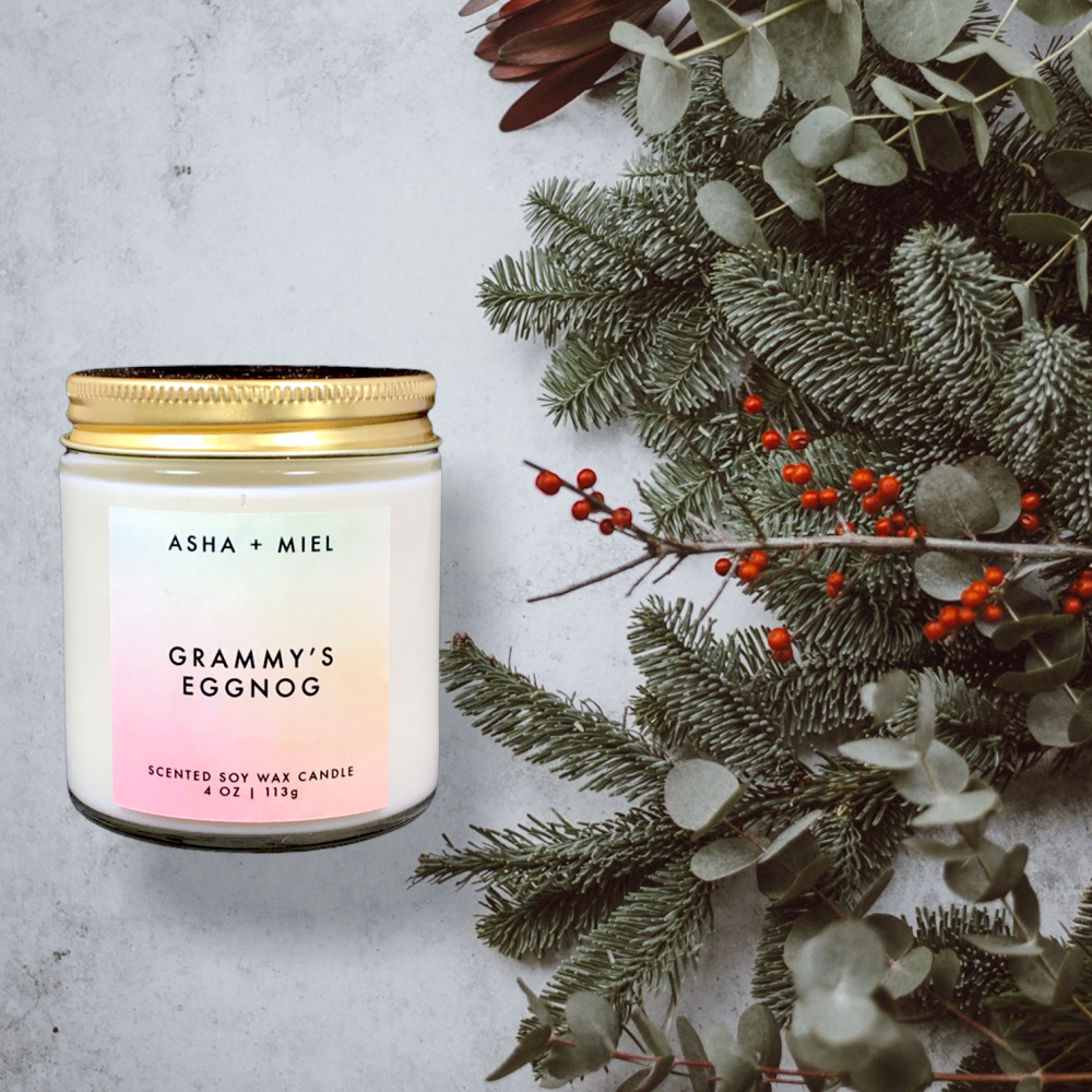 4 Ounce jar of Grammy's Eggnog Candle on background of Christmas Greenery