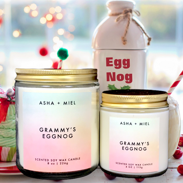 One 8 ounce and one 4 ounce Grammy's Eggnog Candle in glass jars with gold tops on background of table with Egg Nog, berried and a cupcake