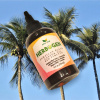 Red Pimento Hair Growth Oil, Jamaican Black Castor Oil, Stinging Nettle Hair Oil 4 oz bottle on decorative palm tree background