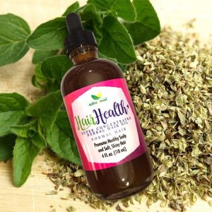 Super Concentrated Herbal Hair Oil, 4 oz glass dropper bottle on a background of herbs